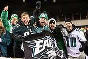 Philadelphia Eagles fans hold up a team flag as they yell and cheer for the team during the NFL NFC Wild Card football game against the New Orleans Saints on Saturday, Jan. 4, 2014 in Philadelphia. The Saints won the game 26-24. ©Paul Anthony Spinelli