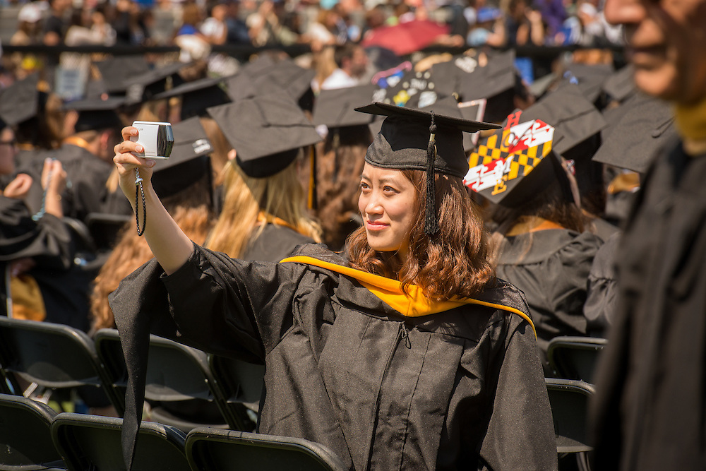 College graduate taking a photo of herself in Baltimore, Maryland, USA