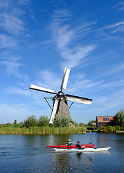 Two men in kayaks in canal in front of historic windmill at Kinderdijk UNESCO World Heritage Site in The Netherlands