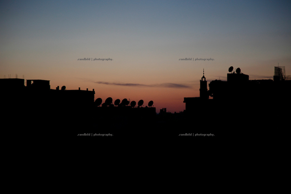 general view over roof tops of the city center of Deir az-Zor during sunset. Residents of eastern syrian town Deir az-Zor joined arab spring protests against the regime of Bashar al-Assad from its early beginning in March 2011. Since summer 2012 the town with few hundred thousand inhabitants is embattled between the Syrian Army and different opposing rebel groups like Free Syrian Army and Jabhat al-Nusra. Deir az-Zor is target to constant shelling by artillery, war planes and short range missiles. Almost 70 percent of the town is rebel held while government forces remain in control over some residental areas and a strategic important airport. Deir az-Zor is widely damaged and some areas almost totally destroyed by fierce and long lasting battles. All direct road connections to Deir az-Zor are cut and fighters and returning residents as well depend on one provisional supply line across the Euphrates river which is regularly targeted by government snipers.