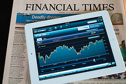 iPad 3 tablet computer with financial app and business newspapers