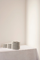Three stacks of plates and cutlery on table