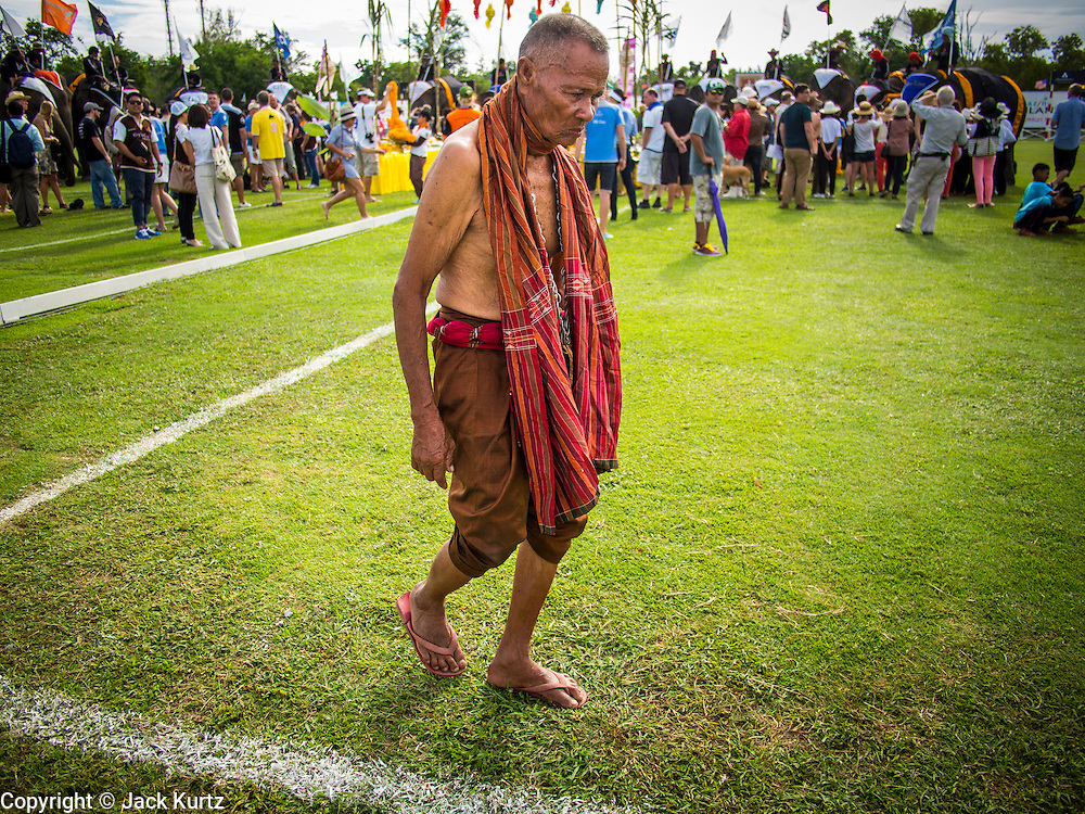 """29 AUGUST 2013 - HUA HIN, PRACHUAP KHIRI KHAN, THAILAND: A """"Khru Ba Yai"""" or Elephant Spirit Man, walks off the field after participating in a blessing for the elephants before the King's Cup Elephant Polo Tournament in Hua Hin. The tournament's primary sponsor in Anantara Resorts and the tournament is hosted by Anantara Hua Hin. This is the 12th year for the King's Cup Elephant Polo Tournament. The sport of elephant polo started in Nepal in 1982. Proceeds from the King's Cup tournament goes to help rehabilitate elephants rescued from abuse. Each team has three players and three elephants. Matches take place on a pitch (field) 80 meters by 48 meters using standard polo balls. The game is divided into two 7 minute """"chukkas"""" or halves. There are 16 teams in this year's tournament, including one team of transgendered """"ladyboys.""""    PHOTO BY JACK KURTZ"""