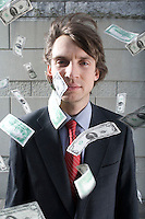 Busines man surrounded by falling money outdoors portrait