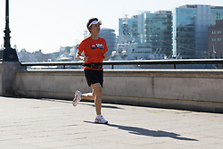 © Licensed to London News Pictures. 05/05/2018. London, UK. A jogger runs along the Thames path during hot and sunny weather near the River Thames in London this morning. Photo credit: Vickie Flores/LNP