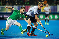 Germany's Linus Butt is tackled by Jonathan Bruton Ireland v Germany - Unibet EuroHockey Championships, Lee Valley Hockey & Tennis Centre, London, UK on 23 August 2015. Photo: Simon Parker