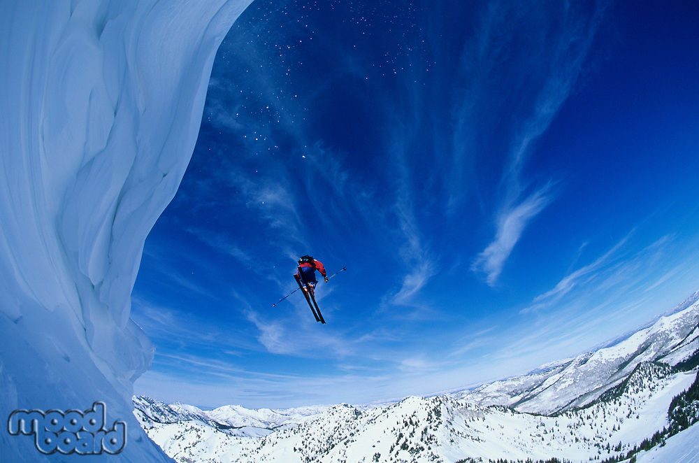 Skier jumping from mountain ledge