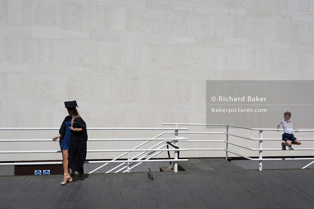 A young boy watches a lady graduate taking a selfie photo of herself after her graduation eremony, in celebration of her university academic achievement, outside the Festival Hall, on 20th July 2017, on the Southbank, London, England.