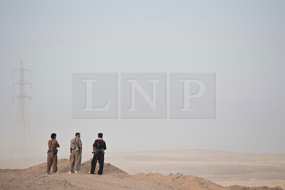 © Licensed to London News Pictures. 30/09/2015. Kirkuk, Iraq. Kurdish peshmerga fighters look in to no man's land and ISIS controlled territory as they prepare to take part in an offensive to capture 11 villages from the Islamic State near Kirkuk, Iraq.<br /> <br /> Supported by large amounts of coalition airstrikes, members of the Iraqi-Kurdish peshmerga today (30/09/2015) took part in an offensive to take seven villages across a large front near Kirkuk, Iraq. By mid afternoon the Kurds had reached most of their objectives, but suffered around 10 casualties all to improvised explosive devices. All seven villages were originally Kurdish and settled with other ethnic groups during the Iraqi Arabisation process of the 1970's and 80's. Photo credit: Matt Cetti-Roberts/LNP