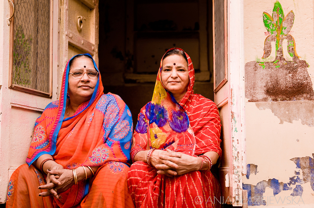 India, Jodhpur. Two Rajasthani ladies wearing red saris sitting ath the front of their house in the old part of Jodhpur.