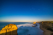 The Twelve Apostles sea stack formations on the Great Ocean Road, lit by the light of the rising nearly Full Moon off camera to the east, with Orion setting in the west over the cliffs. <br /> <br /> This is a stack of 8 x 20 second exposures for the ground and sea, to smooth noise and the waves, plus a single 20-second exposure for the sky to minimize trailing, all at f/2.5 with the Rokinon 14mm lens and Canon 6D at ISO 800. Serves as a good demonstration of Rule of Thirds framing and composition.