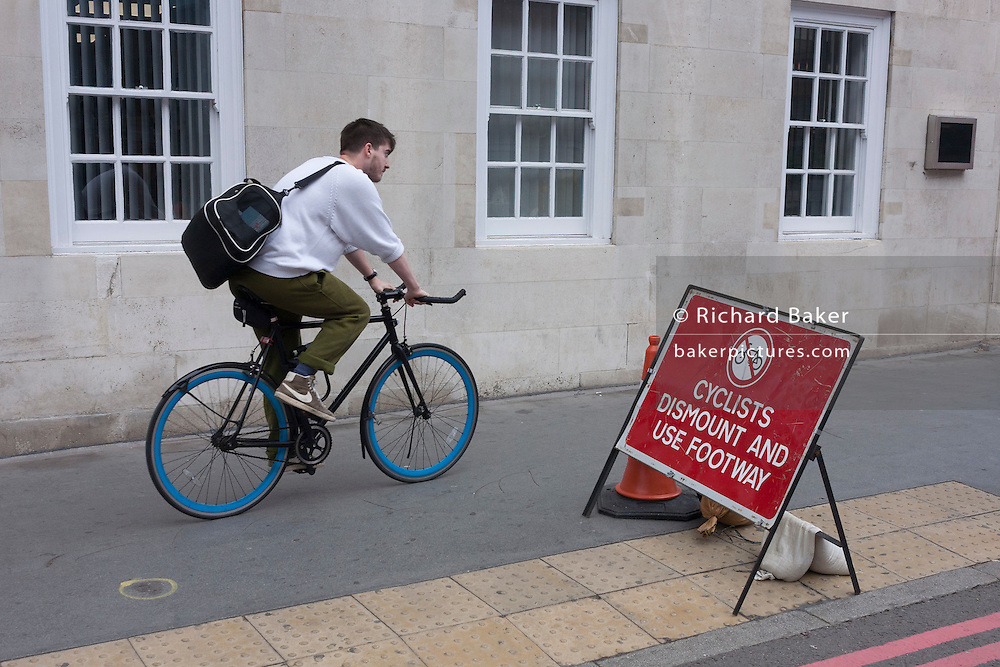 A rider ignores a cyclist's dismount sign on the southern side of London's Tower Bridge, closed for repairs to traffic and disrupting this major Thames crossing and surrounding roads for the next three months.