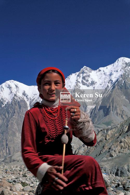 A Kirghiz girl spins wool on Mt. Kunlun, Pamir Plateau, Xinjiang Province, Silk Road, China
