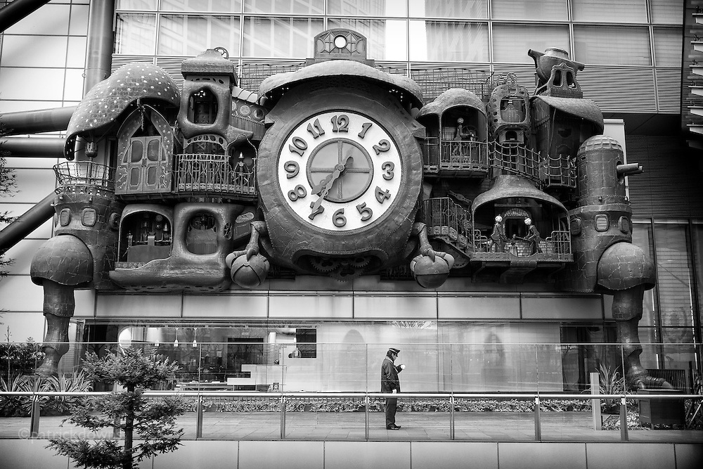 Watch watcher: A security guard at Shiodome Plaza in Toyko checks his watch while standing guard, oblivious of the giant clock. The whimsical and strange sculpture adorns a high-rise there.<br /> <br /> The giant clock is at the Nittele Tower (headquarters of Nippon Television). It was designed by Hayao Miyazaki, the renowned director and co-founder of Studio Ghibli, and while it&rsquo;s not exactly drawn from his 2004 film Howl&rsquo;s Moving Castle, it&rsquo;s been likened to the aesthetic of the anime classic.<br /> <br /> The clock is huge: over 20 tons of copper and steel, three stories high and 60 feet wide. Besides chiming out the time, there are over 30 mechanical vignettes at appointed hours, including cannons, a couple of blacksmiths, a wheel spinner, boiling teapot and two bell-headed piston crankers. They all move in a delicate and industrious ballet, some reminiscent of a cuckoo clock and others like 19th century tin toys.<br /> <br /> The clock springs to life four times on Monday to Friday, with an extra show on Saturdays and Sundays. Each performance begins about four minutes ahead of the hour, and you can see it from many different spots around the Nippon TV tower. But get as close as you can so you can really see the detail. Anime fan or not, Miyazaki&rsquo;s clock is crazy with detail.