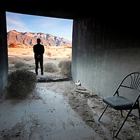 man standing at the threshold of the manmade and the nautral landscapes conjuring notions of environmental contrast. taken near the sandia mountains of albuquerque, new mexico.