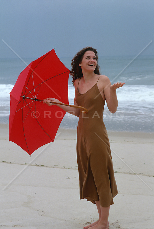 woman at the beach holding an umbrella  in East Hampton, NY; deciding if its raining