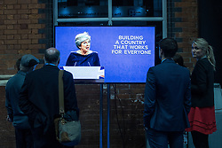 © Licensed to London News Pictures . 04/10/2017. Manchester, UK. Delegates watch Prime Minister THERESA MAY deliver her keynote speech on a screen in the conference exhibition on the fourth and final day of the Conservative Party Conference at the Manchester Central Convention Centre . Photo credit: Joel Goodman/LNP
