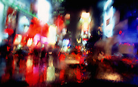 Artistic view of the neon lights of Times Square New York City, diffused through the rain on a car windshield.