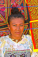 Kuna Indian woman (wearing Mola embrodery blouse, with Mola handicrafts in background), Wichub Wala Island, San Blas Islands (Kuna Yala), Caribbean Sea, Panama