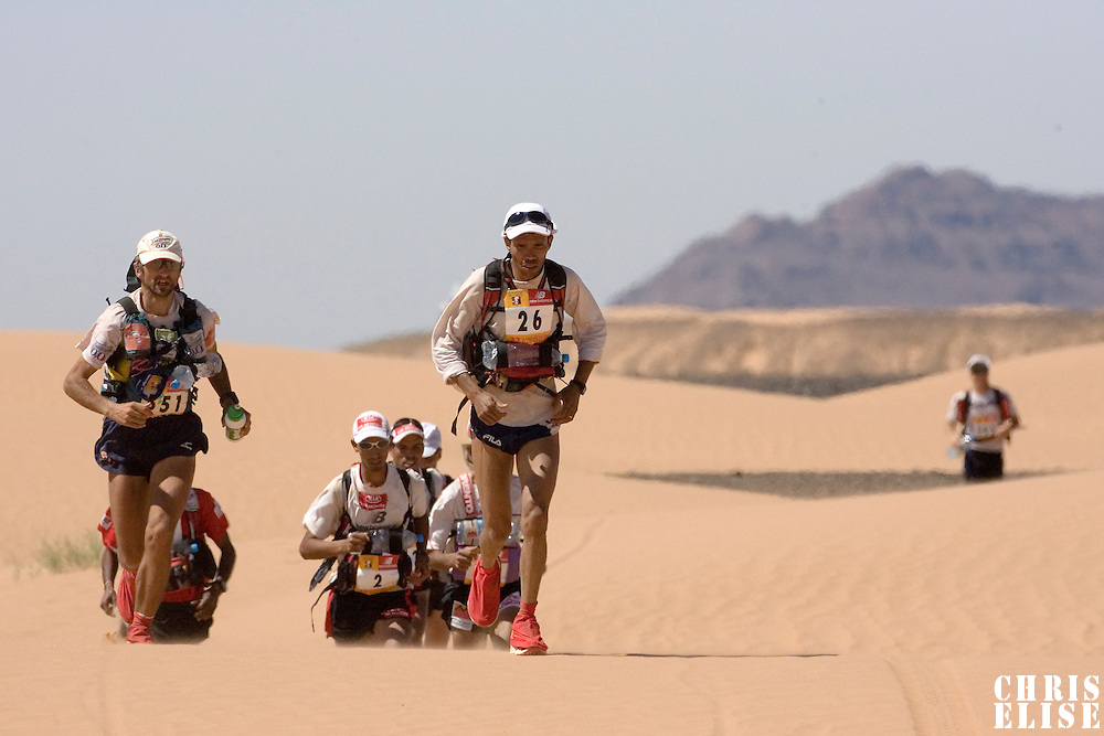 30 March 2007: #26 Aziz El Akad, #551 Aubeso Martine Jorge, #2 Samir Akhdar and others participants run over small dunes in oued Beg'a during fifth stage of the 22nd Marathon des Sables between west of Kfiroun and erg Chebbi (26.22 miles). The Marathon des Sables is a 6 days and 151 miles endurance race with food self sufficiency across the Sahara Desert in Morocco. Each participant must carry his, or her, own backpack containing food, sleeping gear and other material.