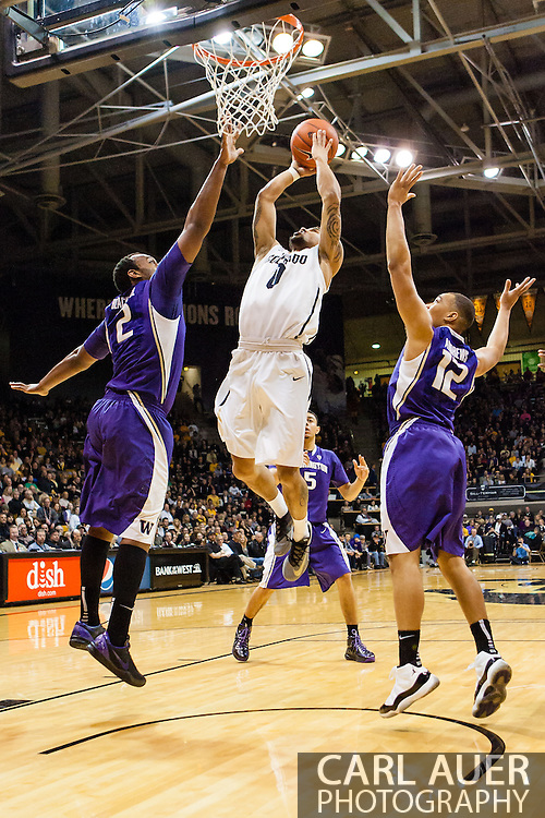 February 9th, 2014:  Colorado Buffaloes junior guard Askia Booker (0) splits between Washington Huskies senior forward Perris Blackwell (2) and sophomore guard Andrew Andrews (12) for a lay up in the first half of the NCAA Basketball game between the Washington Huskies and the University of Colorado Buffaloes at the Coors Events Center in Boulder, Colorado