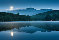 A setting supermoon reflects Grandfather Mountain into Julian Price Memorial Lake during the blue hour of morning along the Blue Ridge Parkway in Western North Carolina.  Julian Price Lake is located at mile marker 297 along the Blue Ridge Parkway near the towns of Blowing Rock and Boone in North Carolina.  The 47-acre lake was created by damming Boone Fork.  The campground that surrounds the lake is the largest facility along the Blue Ridge Parkway.