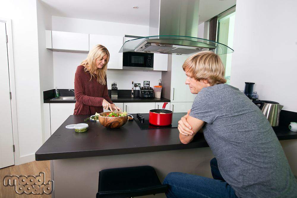 Man looking at woman cutting vegetable in kitchen