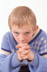 Portrait of young boy with crossed hands looking thoughtful,