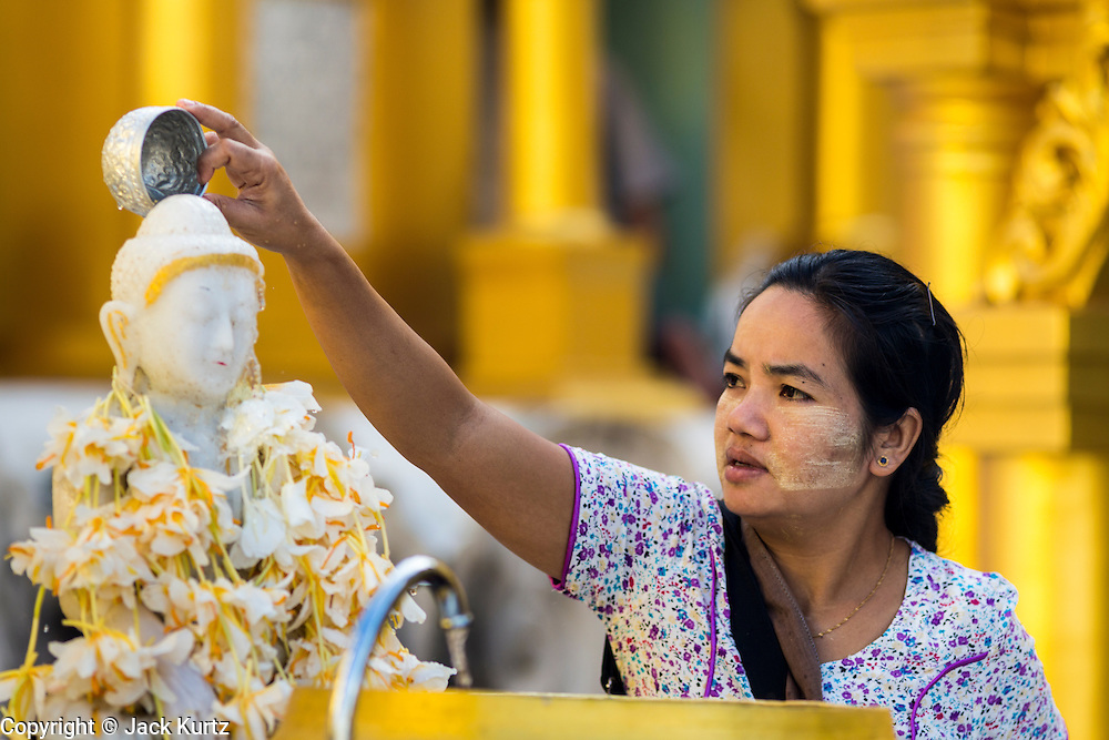 15 JUNE 2013 - YANGON, MYANMAR: A woman bathes at a statue of the Buddha at Shwedagon Pagoda. Shwedagon Pagoda is officially known as Shwedagon Zedi Daw and is also called the Great Dagon Pagoda or the Golden Pagoda. It is a 99 meter (325 ft) tall pagoda and stupa located in Yangon, Burma. The pagoda lies to the west of on Singuttara Hill, and dominates the skyline of the city. It is the most sacred Buddhist pagoda in Myanmar and contains relics of the past four Buddhas enshrined: the staff of Kakusandha, the water filter of Koṇāgamana, a piece of the robe of Kassapa and eight strands of hair from Gautama, the historical Buddha. Burmese believe the pagoda was established as early ca 540BC, but archaeological suggests it was built between the 6th and 10th centuries. The pagoda has been renovated numerous times through the centuries. Millions of Burmese and tens of thousands of tourists visit the pagoda every year, which is the most visited site in Yangon. PHOTO BY JACK KURTZ