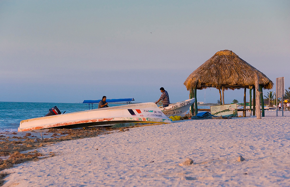 Celestun, Mexico -Jan 17 : Mexican men beside upside down boats prepare for work on the beach at dawn on 17 Jan 2007 at Celestun