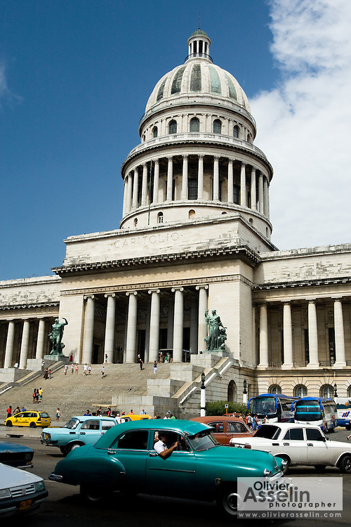 A vintage American car drives by the national capitol building in central Havana, Cuba on Wednesday July 23, 2008.
