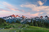 The setting sun casts a glow on the Tatoosh Range from Mazama Ridge's Skyline Trail in Mount Rainier National Park, Washington State, USA