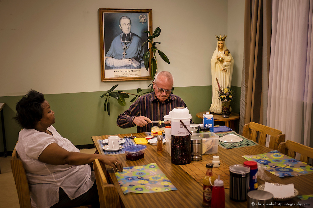 (2013) In company of a church community member, Father Hermann eats dinner at the mess hall of the church in Pioneers Park where he lives in a small apartment.