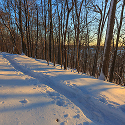 A snowy trail winds through the forest above Indian Hill Reservoir in West Newbury, Massachusetts.
