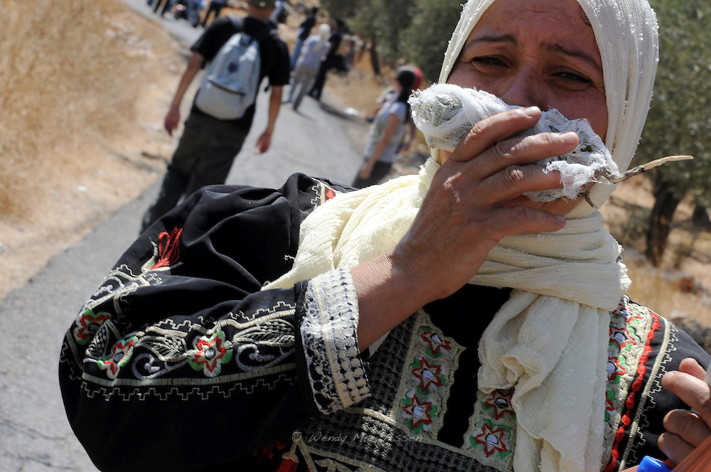 A Palestinian woman is holding herbs in front of her mouth to protect her from not breathing in teargas that the Israeli soldiers shoot at the weekly demonstrators by the controversial serparation wall in the West Bank village of Bil'in. Palestine
