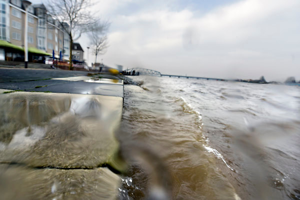 Netherlands, Nijmegen, The Netherlands, 9-1-2018 De Waalkade is afgesloten voor verkeer en het water van de Waal, Rijn, klots tegen en soms over de kaderand. Dagjesmensen en nieuwsgierigen komen al kijken,de coupures tussen de Waalkade en de stad zijn afgesloten. Er is wel al wat schade aan de kade door wegspoelend zand en er ligt al twee weken een binnenvaartschip aangemeerd met motorpech die ook schade toebrengt aan de pas vernieuwde kade.Foto: Flip Franssen