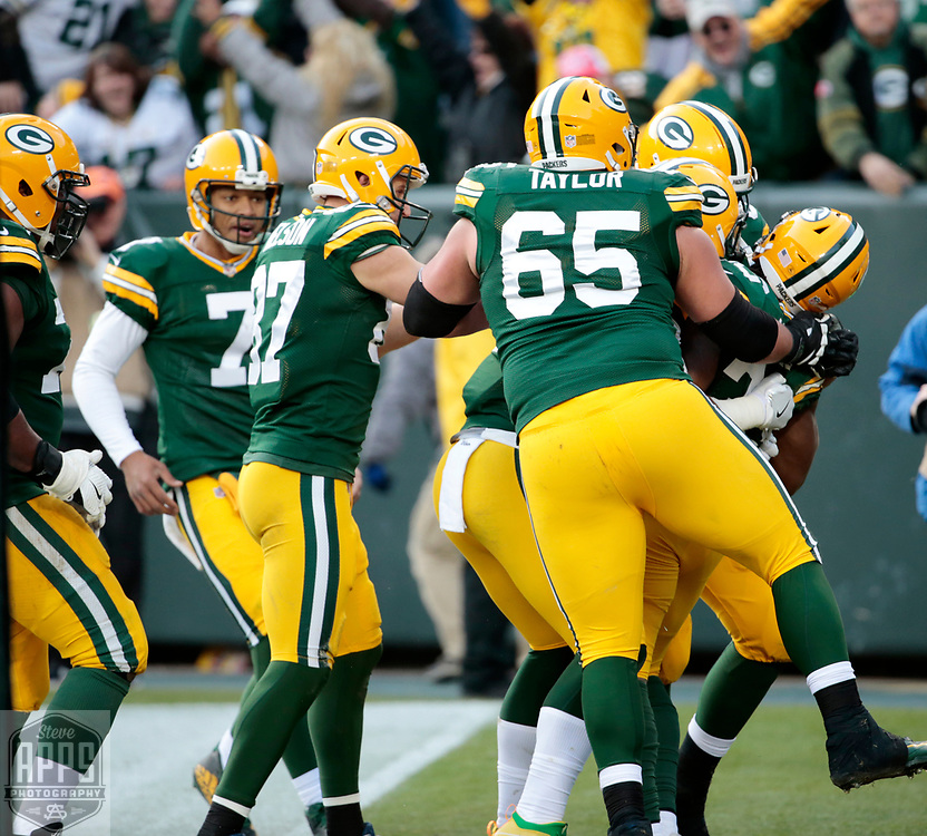 Green Bay Packers running back Aaron Jones (33) is mobbed by teammates after scoring a 20-yard touchdown in Overtime for the win. <br /> The Green Bay Packers hosted the Tampa Bay Buccaneers at Lambeau Field in Green Bay,  Sunday, Dec. 3, 2017. The Packers won in 26-20 in Overtime.   STEVE APPS FOR THE STATE JOURNAL.