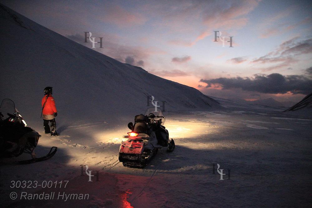 Russian snowmobile guide surveys frozen landscape in dim light of waning polar night between Longyearbyen and Barentsburg in January; Svalbard, Norway.