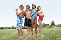 Two young girls and boys in swimsuits in field holding water pistols portrait
