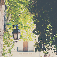 an old iron street lamp seen between the trees of st guilheim le desert