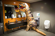 UNITED KINGDOM, London: 27 October 2017 A cosplay fan dressed as an inflatable Tyrannosaurus Rex tries to wash his hands in the bathroom during the MCM London Comic Con. The convention, which runs all this weekend at the Excel Centre, will see thousands of cosplay and comic book fans visit the venue. Rick Findler / Story Picture Agency