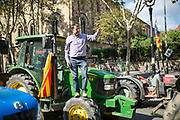 Farmer jumps on his tractor wheel during the Catalunya Farmers Union protest in Gran Via de les Corts Catalanes Editorial and Commercial Photographer based in Valencia, Spain | Portraits, Hospitality, News, Sports, Media Coverage for Events