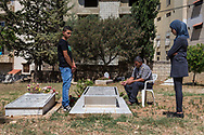"""Rafaat, his son Doread and 12-year-old daughter Rokaca stand over the grave of Yusra and her youngest child in Damour, Lebanon on Sunday, June 8, 2014. <br /> <br /> According to Rafaak, his then-employer/landlord denied any involvement in the deaths, but offered him """"hush money"""" moments after the bodies were pulled from the pond.  Rafaak refused, and promptly visited local police the next day to file a report, only to be dissuaded by them from doing so. Later that evening, Rafaak alleges that his then-employer/landlord attempted to run him and his children down as they walked down a street in search of a new place to live."""