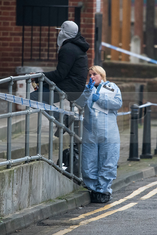 © Licensed to London News Pictures. 09/01/2018. London, UK. Police forensics talk to a local resident at the scene in Stoke Newington where a 34 year old man has died after being assaulted. Officers arrived and found the victim suffering from stab injuries. He was taken to an east London hospital by ambulance where he died just before midnight on 8/1/2018. A murder investigation has been launched. Photo credit: Ben Cawthra/LNP