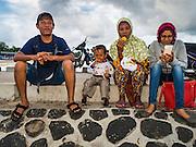 18 JULY 2016 - KUTA, BALI, INDONESIA:  An Indonesian family eats breakfast on the pier at the fish market at Pasar Ikan pantai Kedonganan.   PHOTO BY JACK KURTZ