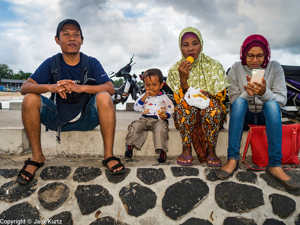 18 JULY 2016 - KUTA, BALI, INDONESIA:  An Indonesian family eats breakfast on the pier at the fish market at Pasar Ikan pantai Kedonganan.   PHOTO BY JACK KURTZ