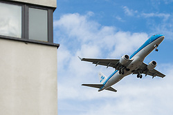 "London, UK. 17 June, 2019. An aircraft on the final approach to Heathrow airport passes alongside a building in Hounslow. On 18th June, Heathrow will publish its airspace and future operations consultation on its ""master plan"" for Heathrow expansion following approval in principle of a third runway by MPs last year. Heathrow is expected to increase the number of flights from the current cap of 480,000 per year imposed when Terminal 5 was built to 505,000 per year in 2021 and to 740,000 per year should a third runway be constructed."