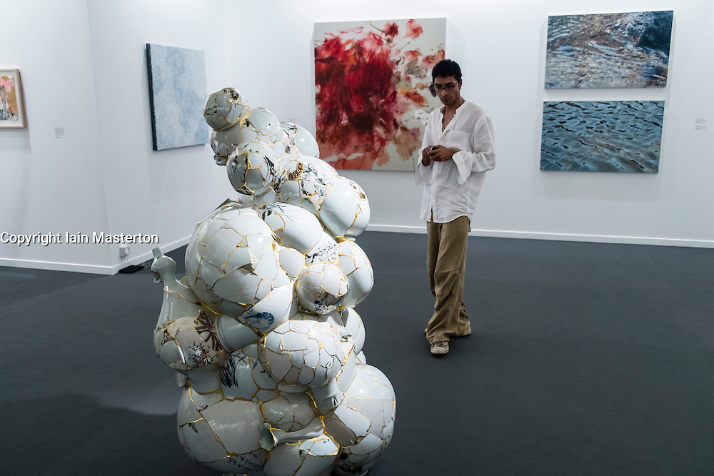 man looking at sculpture at Art Dubai 2014 the leading art fair in the Middle East held at Madinat Jumeirah in Dubai United Arab Emirates