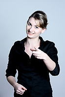 studio shot portraits of a young and cute and expressive woman on a blue grey background pointing his finger