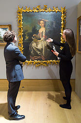 London, July 3rd 2017. Bonhams gallery staff discuss Thomas Hudson's Portrait of Albinia Bertie As A Young Girl, Seated in a Landscape holding a Basket of Doves, a Spaniel at Her Feet, which is expected to fetch £60-80,000 in their Old Master Paintings sale.